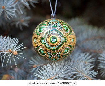 Christmas ball painted with indian ethnic ornamet hanging on the brunch of New Year tree. Holiday winter wallpaper.