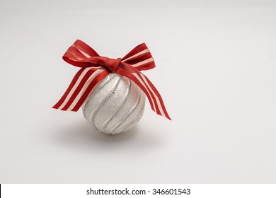 Christmas ball with red ribbon isolated on white background