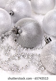 Christmas ball and silver beads in snow.