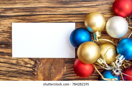 Christmas balls with blank business card on the table. New year background. Top view.