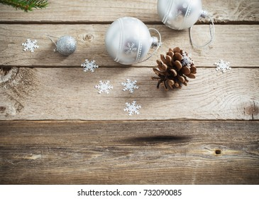 Christmas balls and cones on dark wooden background