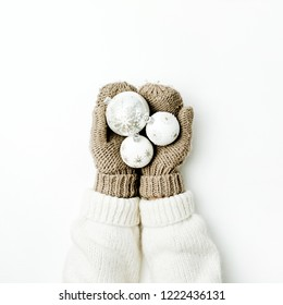 Christmas balls decoration in female hands in knitted mittens on white background. Flat lay, top view Christmas / New Year / Winter festive composition.