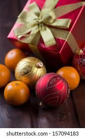 Christmas balls, gift box and ripe tangerines, vertical shot