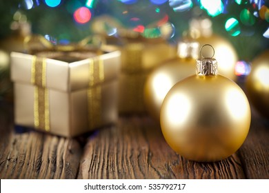 Christmas balls and gift boxes on wooden table and abstract background