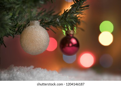 Christmas balls hanging from the pine above the fake snow