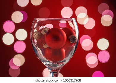Christmas balls inside the wine glass on background of festive lights.