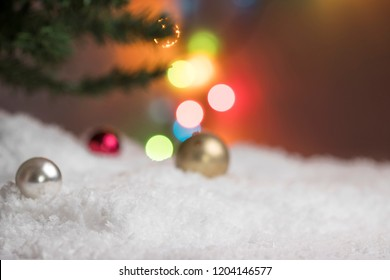 Christmas balls lying in the fake snow under the pine branch and colorful light behind