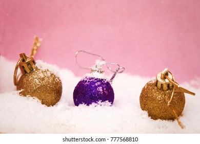 christmas balls on snow and pink background