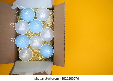 Christmas balls on the Christmas tree in an open cardboard box on a yellow background. The art collage. The view from the top. Hand-drawn in white.
