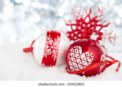 Christmas balls with painted heart  and ribbon against holiday lights.