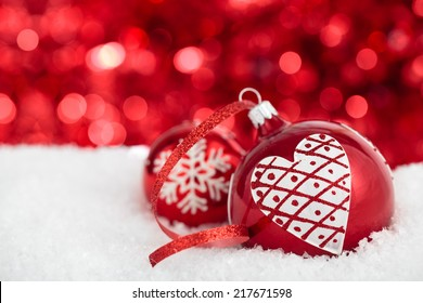 Christmas balls with painted heart and snowflake against red holiday lights.
