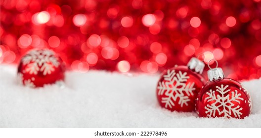 Christmas balls with painted   snowflakes against red holiday lights.