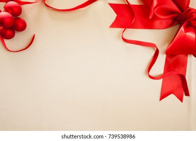 Christmas balls, ribbon and red silk bow on an off white satin background with plenty of room for Holiday announcements.