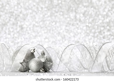 Christmas balls and ribbons decoration on shiny silver background