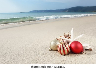 christmas balls and seashells on the beach near the sea - Beach Christmas Pictures