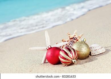 Christmas balls and seashells on the beach near the sea.