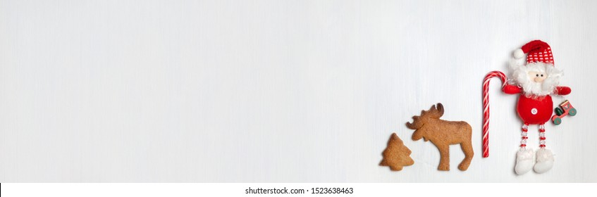 Christmas banner with cookies and Christmas toy or attribute on a white wooden background. Top view, copyspace, no people