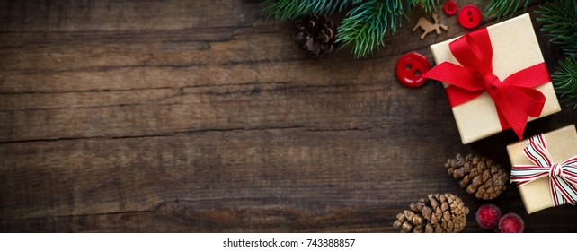 Christmas banner with gifts, fir branches pine cones and seasonal ornaments against dark rustic wooden background. Overhead view with copy space for your text
