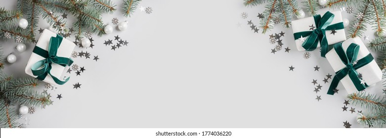 Christmas banner with gifts, xmas fir branches and white decor on grey. Merry christmas card. Winter holiday. Happy New Year. Space for text