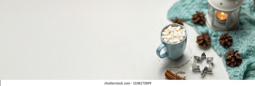Christmas banner with a hot latte, a flashlight, a blanket and a Christmas attribute on a white background. Top view, copy space, no people