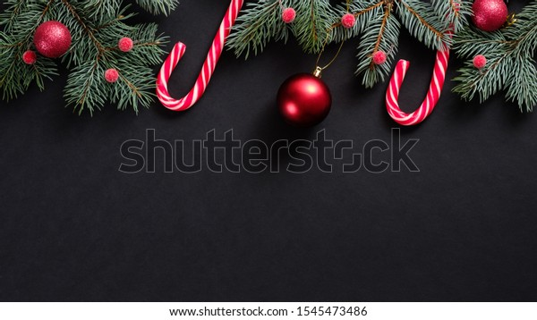 Christmas banner mockup. Top frame border made of candy cane and fir tree branches on black background. Christmas or New year holidays concept