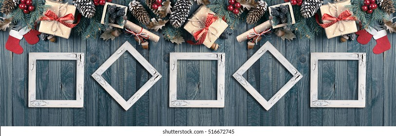 Christmas banner with photo frames, spruce, gift box, Santa Claus boots, mitten and scroll in vintage style on wooden shabby boards background