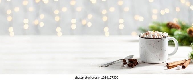 Christmas banner with white cup with hot chocolate and marshmallows on with cinnamon sticks and fir xmas tree branches with beautiful garland lights. New year celebration