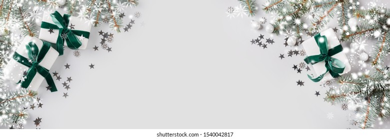 Christmas banner with xmas tree and white gifts with green velvet ribbon on grey background. Merry christmas card. Winter holiday. Happy New Year. Space for text