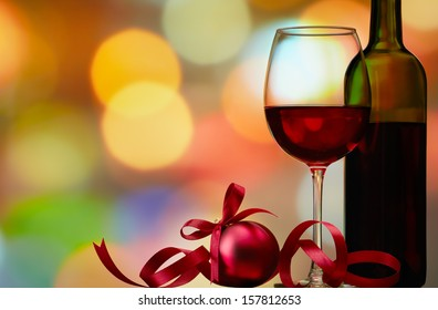 christmas bauble with red wine against colorful bokeh lights background