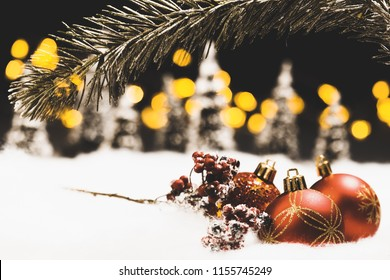 Christmas bauble still life in snow with silent black night background and bokeh lights in fir tree forest setting with focus on front