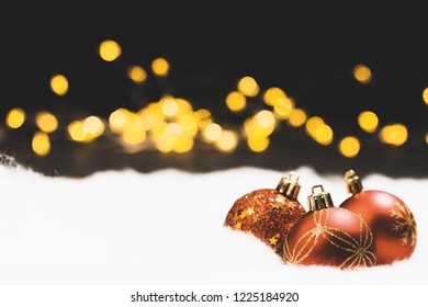 Christmas bauble still life in snow with silent black night background and bokeh lights