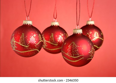 Christmas baubles hanging over red background