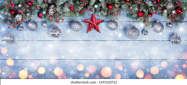 Christmas Baubles With Star In Fir Branches On Snowy Wooden Plank