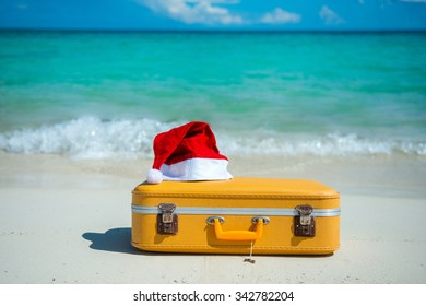 Christmas beach holidays in the Caribbean, with a suitcase and Santa Claus hat. Perfect Getaway.