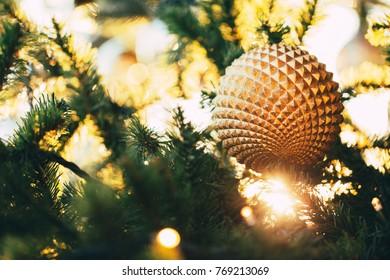 Christmas beautiful geometric sphere on fir tree in beautiful light.