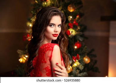 Christmas. Beautiful smiling woman. Manicure nails. Makeup. Healthy long hair style. Elegant lady in red dress over christmas tree lights background. happy new year.