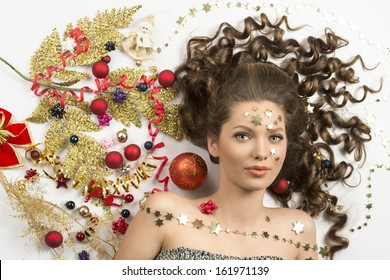 christmas beauty close-up portrait of sensual curly brunette girl with splendid eyes surrounded by colorful xmas decorations, red baubles, golden branch, ribbon and stars on her face.