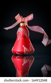 Christmas bell with red ribbon on black background