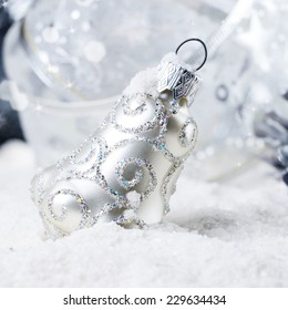 Christmas bells baubles on snow over bright background