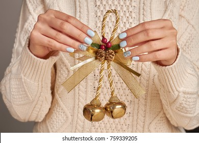 Christmas bells with golden bow. Handmade ornaments and decorations. Bring festive spirit to your home. Beautiful manicure.