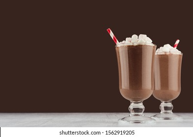 Christmas beverage - hot chocolate with marshmallows and red striped straw  in elegant dark brown interior, copy space.