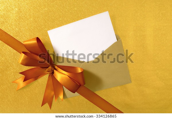 Christmas or birthday card, gold diagonal gift ribbon bow, shiny paper background, copy space