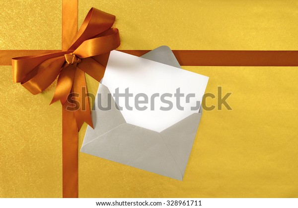 Christmas or birthday card, gold gift ribbon bow on shiny paper background, silver envelope , copy space
