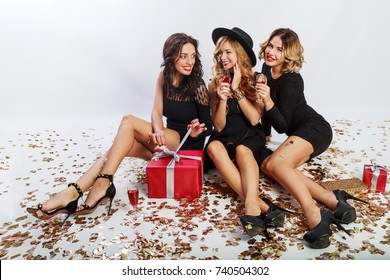 Christmas  or birthday  party.  Three  beautiful women  sitting on floor and  drinking cocktails.  Best friends unpack gifts. Golden sparkling confetti. white background. Wavy hairstyle.