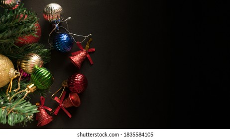 Christmas black background with decoration, red berry, bauble and fir tree branch