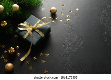 Christmas black gift with decorative golden ribbon on black surface. Close up. Xmas Greeting card.