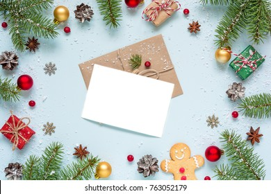 christmas blank greeting card in frame made of fir tree branches, decorations and gift boxes over blue background. mock up. flat lay. top view