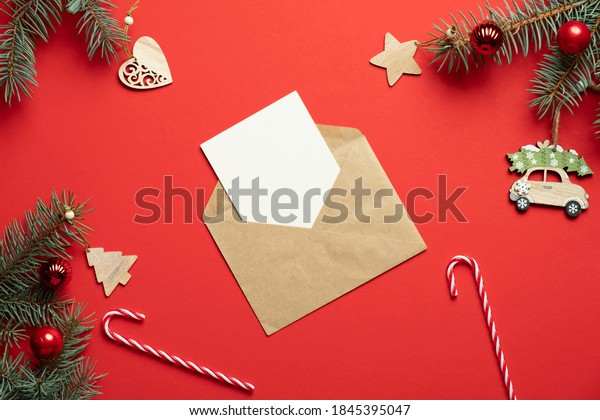Christmas blank greeting card in kraft paper envelope and Xmas decorations on red background. Flat lay, top view. Christmas letter to Santa concept.