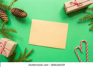 Christmas blank greeting card mock-up scene. Festive winter composition. Craft envelope, pine cone, gift box and fir tree branch on green background. Flat lay, top view, copy space.