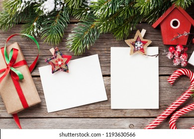 Christmas blank photo frames, birdhouse decor and snow fir tree on wooden table. Top view with space for your greetings